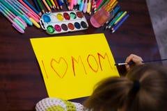 Nettes Kleinkindmädchen schreibt das Text ` I Liebes-Mutter ` durch Farben lizenzfreies stockbild
