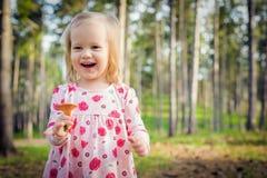 Nettes Kleinkindmädchensammeln vermehrt sich in ein Waldglückliches Kind explosionsartig, das einen Pilz und ein Lachen hält Stockfotografie