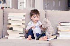 Nettes kluges lustiges kleines Baby mit dem durchdachten ernsten Gesichtsausdruck, der Gläser im Handlesebuchsitzen auf Sofa wi h stockfotografie