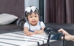 Nettes Lächeln des kleinen Mädchens und macht Foto Lizenzfreie Stockbilder