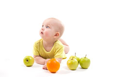 Nettes lächelndes Baby, das auf seinem Magen unter Früchten und dem Schauen liegt Lizenzfreies Stockbild