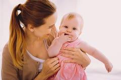 Nettes lächelndes Elternteil beim Betrachten ihres ruhigen durchdachten Babys Stockfoto