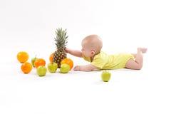 Nettes lächelndes gesundes Kind liegt auf einem weißen Hintergrund unter frui Lizenzfreie Stockfotografie