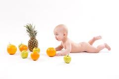 Nettes lächelndes gesundes Kind liegt auf einem weißen Hintergrund unter frui Lizenzfreie Stockbilder