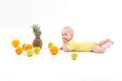 Nettes lächelndes gesundes Kind liegt auf einem weißen Hintergrund unter frui Stockfotografie