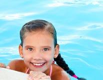 Nettes lächelndes glückliches Kind des kleinen Mädchens im Swimmingpool Stockbild