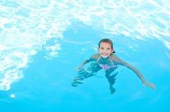 Nettes lächelndes glückliches Kind des kleinen Mädchens im Swimmingpool Stockfotografie