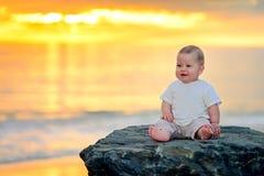 Nettes lächelndes Kind, das auf dem Felsen sitzt Stockbilder