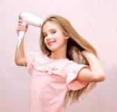 Nettes lächelndes Kind des kleinen Mädchens, das ihr langes Haar mit Haartrockner trocknet stockfotografie