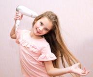 Nettes lächelndes Kind des kleinen Mädchens, das ihr langes Haar mit Haartrockner trocknet stockfoto