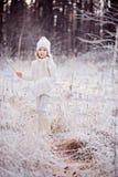 Nettes lächelndes Kindermädchen auf dem Weg in Winter gefrorenem Wald Lizenzfreie Stockfotos