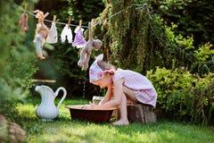 Nettes lächelndes Kindermädchen, das Spielzeugwäsche im sonnigen Sommergarten spielt Lizenzfreies Stockbild