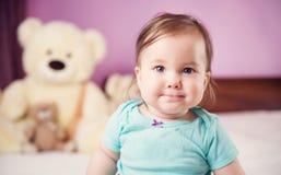 Nettes lächelndes kleines Baby, das auf dem Bett mit weichen Spielwaren sitzt Lizenzfreie Stockbilder