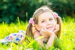 Nettes lächelndes kleines Mädchen, das auf Gras legt stockfotografie
