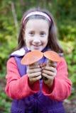Nettes lächelndes kleines Mädchen, das einen Pilz anhält Lizenzfreies Stockfoto