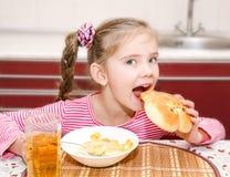 Nettes lächelndes kleines Mädchen, das Frühstückskost aus Getreide mit Milch isst Stockfotos