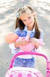 Nettes lächelndes kleines Mädchen, das mit ihrem Spielzeugwagen spielt Stockbilder
