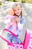 Nettes lächelndes kleines Mädchen, das mit ihrem Spielzeugwagen spielt Stockfoto