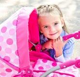 Nettes lächelndes kleines Mädchen, das mit ihrem Spielzeugwagen spielt Lizenzfreie Stockfotos