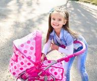 Nettes lächelndes kleines Mädchen, das mit ihrem Spielzeugwagen spielt Lizenzfreies Stockfoto