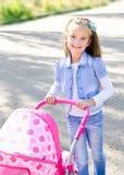 Nettes lächelndes kleines Mädchen, das mit ihrem Spielzeugwagen spielt Stockfotografie