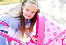 Nettes lächelndes kleines Mädchen, das mit ihrem Spielzeugwagen spielt Lizenzfreies Stockbild