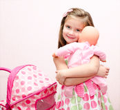 Nettes lächelndes kleines Mädchen, das mit ihrem Spielzeugwagen und -puppe spielt Lizenzfreie Stockfotos