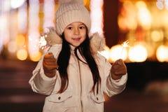 Nettes lächelndes kleines Mädchen mit Bengal-Lichtern auf der Straße am Abend stockfoto