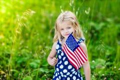 Nettes lächelndes kleines Mädchen mit dem blonden Haar, das amerikanische Flagge hält stockfoto