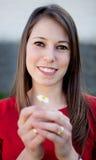 Nettes lächelndes Mädchen, das ein Gänseblümchen hält Stockfotografie