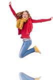 Nettes lächelndes Mädchen in der roten Jacke und in den Jeans lokalisiert Stockfoto