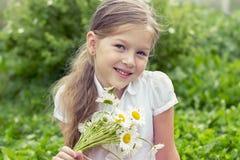 Nettes lächelndes Mädchen mit einem Blumenstrauß von Gänseblümchen Stockfotos