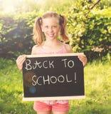 Nettes lächelndes Schulmädchen, das draußen mit der Tafel sonnig steht Stockbilder