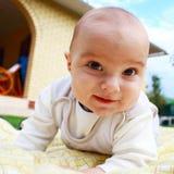 Nettes lächelndes Säuglingsbaby, das am Yard spielt. Lizenzfreie Stockfotografie
