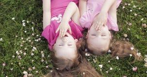 Nettes Lügen des kleinen Mädchens zwei umgedreht auf dem Wiesengras und -blumen, die Luftkuss- und -c$wellenartig bewegenhand her stock footage