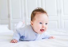 Nettes lachendes kleines Baby, das ihre Bauchzeit genießt Stockbilder