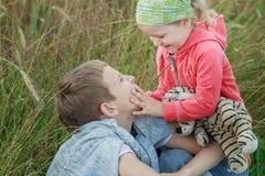 Nettes lachendes Kleinkindmädchen, das ihr Geschwisterbrudergesicht am natürlichen Hintergrund der Sommerwiese berührt Stockfotografie