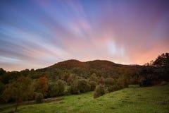 Nettes langes Belichtungsbild, cloudscape über dem Berg im Sonnenuntergang und Herbstfarben lizenzfreie stockbilder