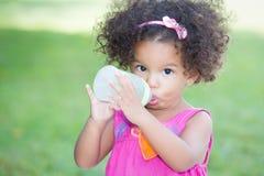 Nettes lateinisches Mädchen, das von einer Babyflasche trinkt Lizenzfreies Stockfoto