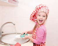Nettes lächelndes kleines Mädchen, das die Teller wäscht Stockfoto