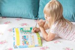 Nettes liitle blondes Mädchen, das auf einem Bett liegt und hometasks im Arbeitsbuch mit einem Bleistift in einer Hand macht Stockfoto