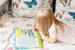 Nettes liitle blondes Mädchen, das auf einem Bett liegt und hometasks im Arbeitsbuch mit einem Bleistift in einer Hand macht Lizenzfreies Stockfoto