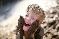 Nettes Little Boy, das draußen im Schlamm mit einem schmutzigen Gesicht spielt stockfotos
