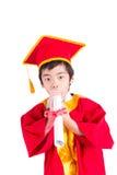Nettes Little Boy, das rote Kleiderkinderstaffelung mit Doktorhut trägt Stockfoto