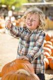 Nettes Little Boy gibt Daumen am Kürbis-Flecken auf Stockfoto