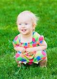 Nettes lustiges Baby, das auf Gras sitzt Stockbild