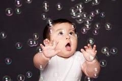 Nettes lustiges glückliches überraschtes Baby mit Blasen lizenzfreie stockbilder