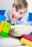 Nettes lustiges kleines Kind, das auf einem Sofa mit bunten Büchern und Spielwaren stillsteht Stockbild