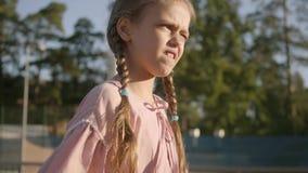 Nettes lustiges Mädchen mit zwei Zöpfen, die draußen Tennis spielen Starkes Kind, das ungefähr einen Schläger und einen Ball hält stock video footage