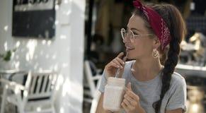 Nettes Mädchen mit Zopf auf Kopf und großen Ohrringhaltungen Café des Sommers im im Freien, stockfotos